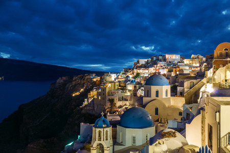 Churches of Oia village at dusk with dramatic sky, Santorini island, Greece Archivio Fotografico