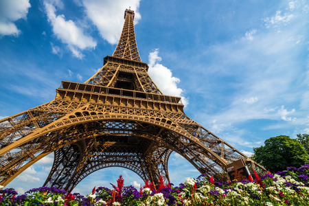 Eiffel Tower: Wide shot of Eiffel Tower with dramatic sky and flowers at late evening, Paris, France Stock Photo