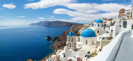 Panoramic view of the Oia village under puffy clouds, Santorini island, Greece 免版税图像