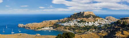 Panorama of the Lindos town and Acropolis on the island of Rhodes under puffy clouds, Greece Archivio Fotografico