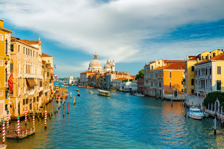Gorgeous view of the Grand Canal and Basilica Santa Maria della Salute during sunset with beautiful clouds, Venice, Italy