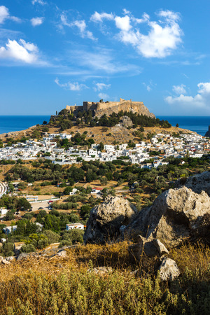 Town of Lindos and Acropolis on the island of Rhodes under puffy clouds, Greece