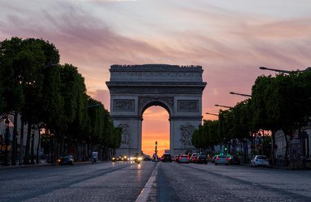 blurr: Arch of Triumph (Arc de Triomphe) with dramatic sunset behind, Paris, France Stock Photo