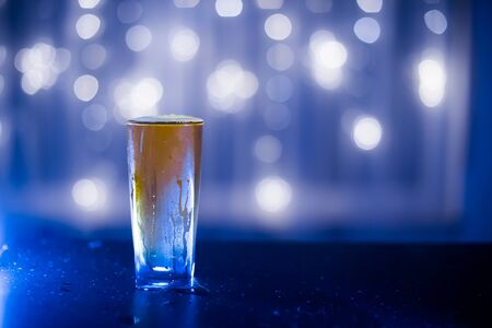 light beer in a figured glass on a black table on a blurred background