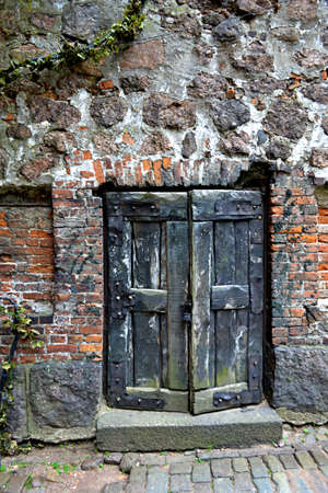 an old wooden door in the wall of the ancient Russian fortress