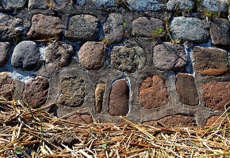 background of the stone wall of large boulders and dry reed Stock Photo