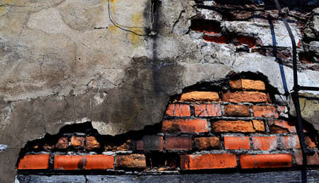 crack in the plaster wall with the exposed brick Stock Photo