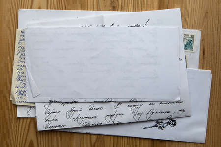 stack of old papers and letters on a wooden background photo