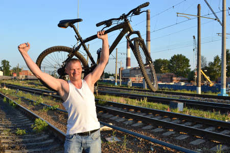 athletic-looking man walking with his bicycle by rail
