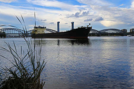 barge comes up from under the bridge on a cloudy day Stock Photo