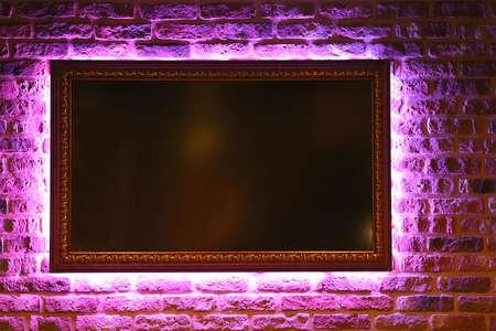 brick background with frame illuminated neon Stock Photo