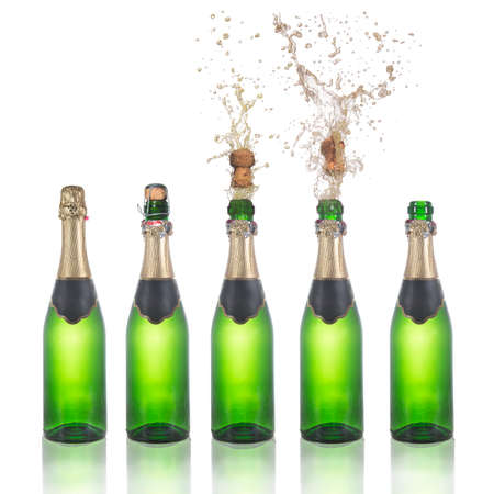 Set of champagne bottles with popping corks . Isolated on white background