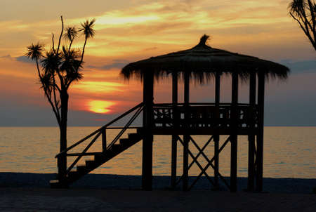Amazing sunset behind bungalow and tree photo