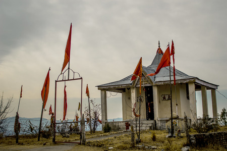 An isolated Indian temple with red flags, on Shimla highway, India
