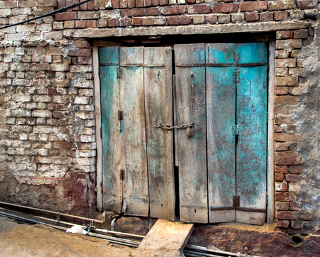 dilapidated wall: an old vintage Indian door with bricks Stock Photo