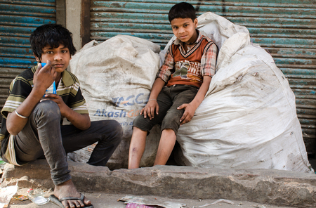 NEW DELHI, INDIA - 23 APRIL 2016 : portrait of two Indian boys sitting on garbage bags Editorial
