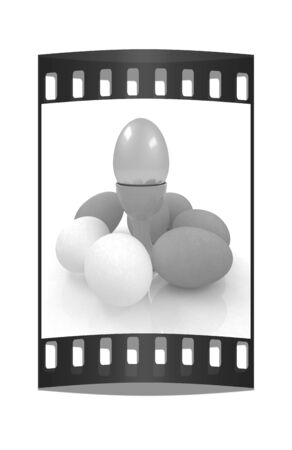 gold eggs: Eggs and gold easter egg on egg cups. The film strip