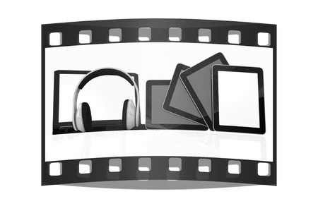 mpg: headphones on the  laptop and  tablet pc on a white background. The film strip Stock Photo