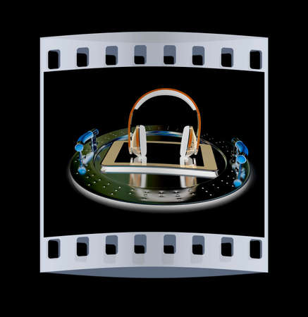 Phone and headphones on metal tray on a black background. The film strip