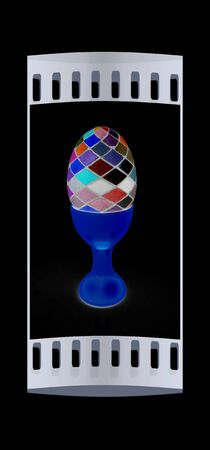 egg cups: Easter egg on gold egg cups on a black background. The film strip