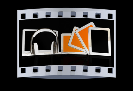 mpg: headphones on the  laptop and  tablet pc on a black background. The film strip