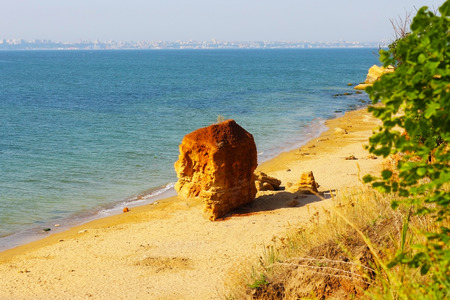 Deserted sandy beach with lonely clay mountain