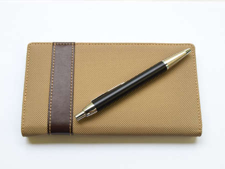 Light brown notebook and pen  cover isolated on white background photo