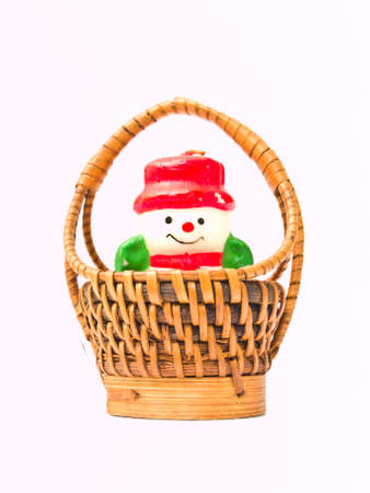 A christmas snow doll candle and a  yellow wicker basket isolated on white background photo