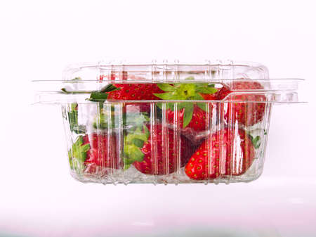 Fresh Strawberry piled in clear plastic box Isolated on white background photo