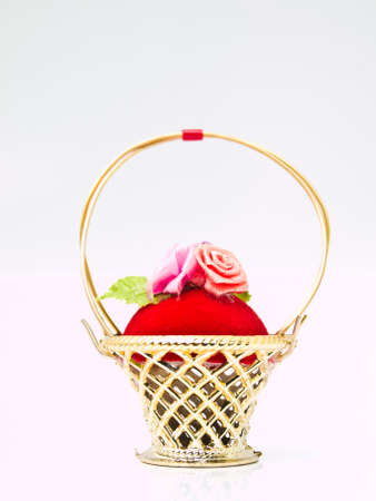 A miniature metalic wicker decorated by roses on a red velvet isolated on white background Stock Photo