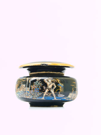A black miniature ceramic jar painted by  tourist destinations in Rome, Italy isolated on white background