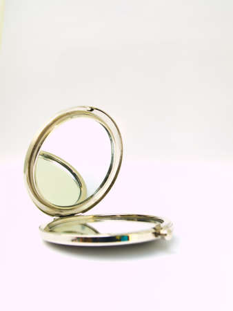 A metalic pocket makeup mirror isolated on white background photo