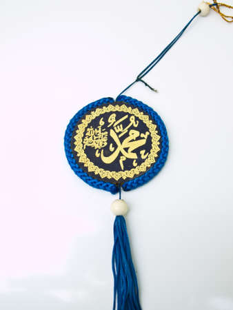 A blue velvet Allah pendent isolated on white background Islamic calligraphy transliterated as  Stock Photo