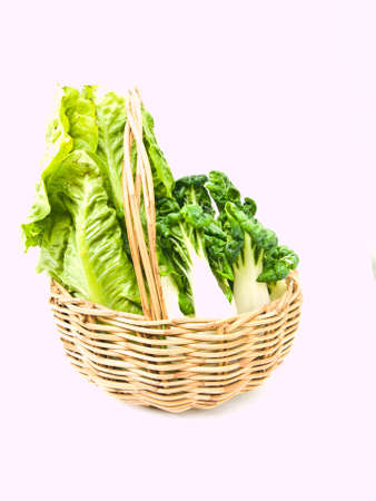 Fresh  baby bok choy and cos salad in ratten basket isolated on white background Stock Photo - 17836845