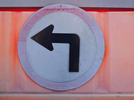 A old turn left road sign on orange barrier photo