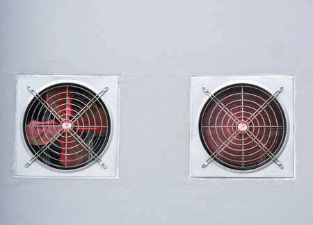 A pair of red industrial ventilated fan on grey wall as background
