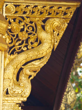 golden wooden carving buttress, Wat Phrathat chomkitti temple in Chiang rai, Thailand  photo