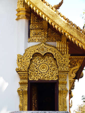 golden wooden carving of entrance gate, Wat Phrathat chomkitti temple in Chiang rai, Thailand  photo