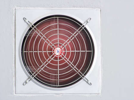 A red industrial ventilated fan on grey wall as background photo