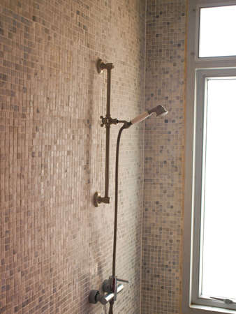 Modern shower faucet with light tiled wall and natural light