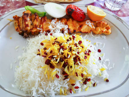 An Iranian grilled chicken and tomatoes served on rice in white ceramic plate photo