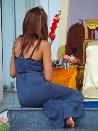 Chiang Mai, Thailand- February 26- A sexy Thai woman with tattooes in her back prostrates herself to worship Buddha image in Chiang Mai, Thailand on February 26, 2011