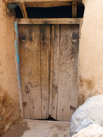 mud and snow: Old wooden doors in Kandovan village in Tabriz, Iran Stock Photo