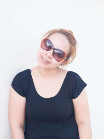 Young Asian lady wearing sunglasses smiling in nature