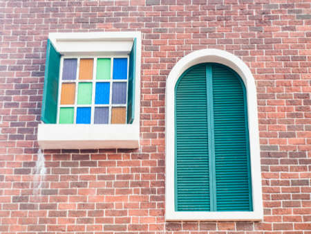 colorful glass and wooden shutter windows in brick wall background photo