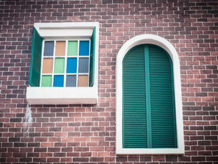 retro colorful glass and wooden shutter windows in brick wall background photo
