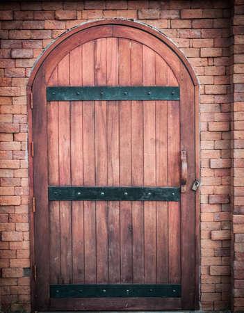 retro grunge wooden gate in brick wall background photo