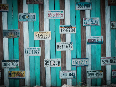 numberplate: PRACHUAP KHIRI KHAN, THAILAND - FEB 23, 2015: Old US car registration plate on wooden wall in Hua Hin, Prachuap Khiri Khan, Thailand. retro style