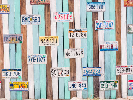 numberplate: PRACHUAP KHIRI KHAN, THAILAND - FEB 23, 2015: Old US car registration plate on wooden wall in Hua Hin, Prachuap Khiri Khan, Thailand.