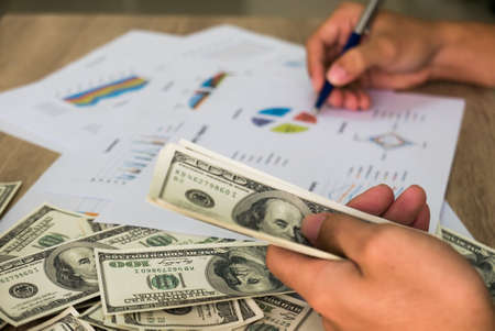 Closeup of Asian male left hand counting bunch of dollars banknotes and his right hand hold ball pen points on business charts background for business, finance, tax and people concept